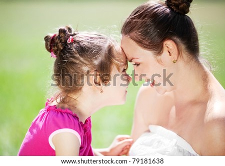 beautiful young mother and her daughter in the park on a sunny summer day talking and laughing (focus on the woman) - stock photo