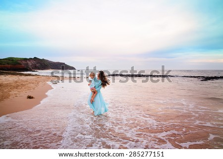 Beautiful young mother and her daughter on a ocean beach - stock photo