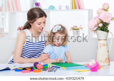 beautiful young mother and her little daughter drawing with pencils on the album. mother and daughter in blue dress  at home. - stock photo