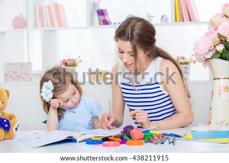 beautiful young mother and her little daughter drawing with pencils on the album.the child is tired - stock photo