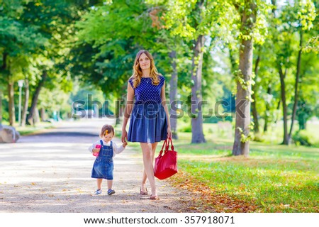 Beautiful young mother and her little daughter walking in summer park. Woman and cute kid girl spending time together. Happy family of two on warm sunny day - stock photo