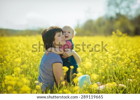 beautiful young mother and her little son are resting in nature - stock photo