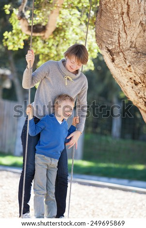 beautiful young mother and her little son enjoying time together and having fun in the park swinging - stock photo