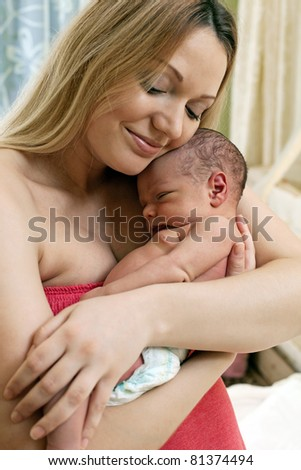 Beautiful young mother and her newborn baby boy - stock photo