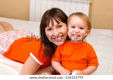 beautiful young mother and her 2,5 year old daughter on the bed at home - stock photo