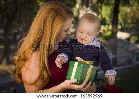 Beautiful Young Mother and Smiling Baby with Wrapped Christmas Gift. - stock photo