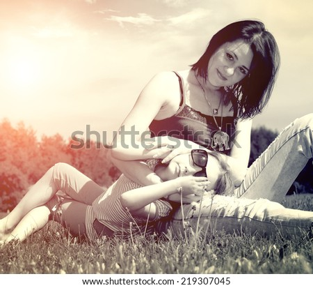 beautiful young mother daughter relaxing sitting grass - stock photo