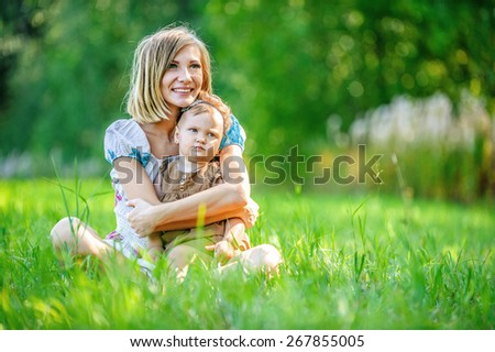 beautiful young mother daughter relaxing sitting grass background summer meadow green grass trees