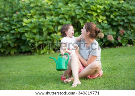 beautiful young mother daughter smiling each other summer meadow green grass trees - stock photo