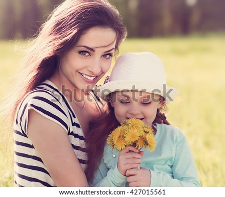 Beautiful young mother embracing her cute daughter with yellow bright flowers on summer background. Closeup portrait - stock photo