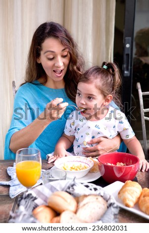 Beautiful young mother feeding her little toddler girl sitting on her lap, breakfast cereal at outdoor home environment. Focus is on toddler.