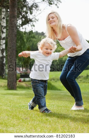 Beautiful young mother helping her adorable little boy to walk - stock photo