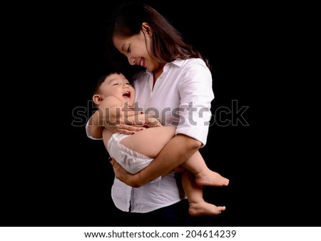 beautiful young mother holding baby boy isolated on black - stock photo