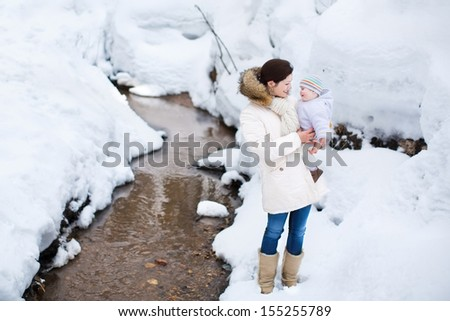 Beautiful young mother holding her baby on a walk in a snowy winter park - stock photo