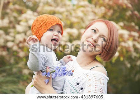 beautiful young mother holding her laughing little daughter  - stock photo