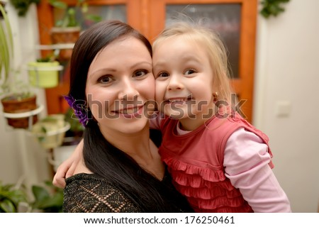 Beautiful young mother holding her sweet little daughter. - stock photo