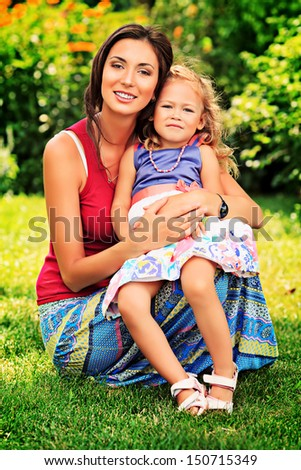 Beautiful young mother holding her sweet little daughter. Outdoors.