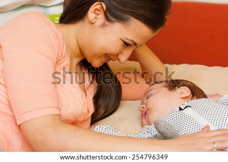Beautiful young mother in bed smiling at her sleeping baby. - stock photo