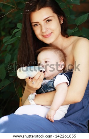 Beautiful young mother is feeding her baby from a bottle outdoor - stock photo