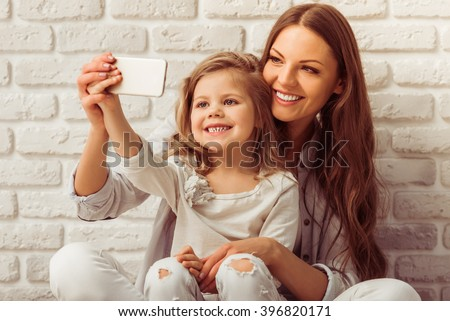 Beautiful young mother is making a selfie with her cute little daughter using a smart phone and smiling, against white brick wall - stock photo