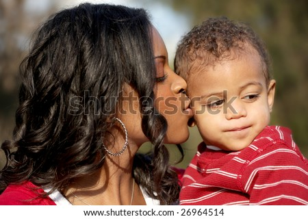 Beautiful young mother kissing her baby boy - stock photo