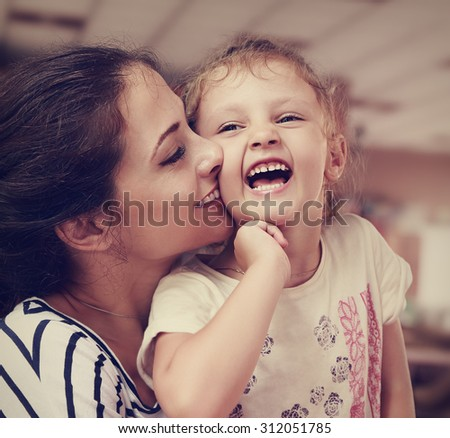 Beautiful young mother kissing her joying happy cute daughter indoor background. Closeup portrait - stock photo