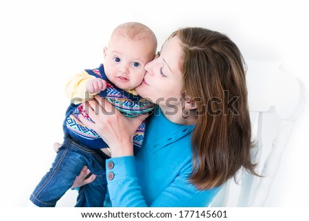 Beautiful young mother kissing her little baby boy both wearing blue knitted sweaters - stock photo