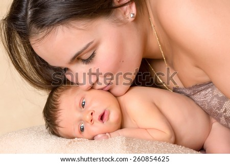 Beautiful young mother kissing her seven days old newborn baby - stock photo