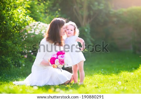 Beautiful young mother nd her adorable little daughter, cute little curly girl in a white dress, playing in the garden, hugging and kissing, with a bunch of red and pink flowers on a sunny summer day - stock photo