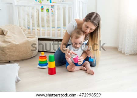 Beautiful young mother playing and teaching her baby boy on floor at living room