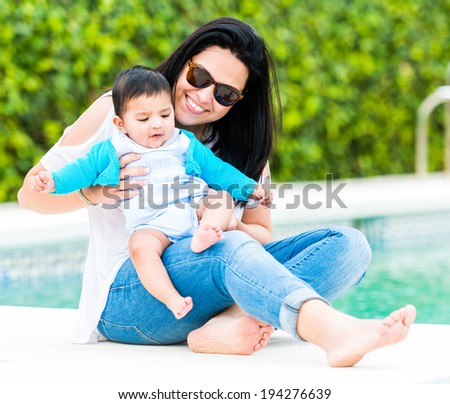 beautiful young mother playing with baby near the swimming pool on a sunny summer day - stock photo