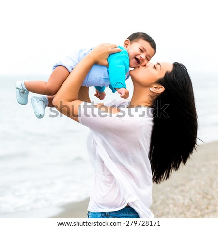 beautiful young mother playing with her baby  on the beach on a sunny summer day - stock photo