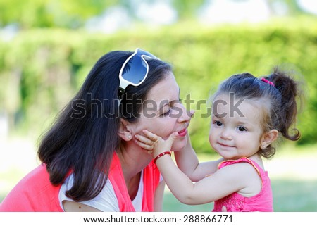 Beautiful young mother playing with her daughter - stock photo