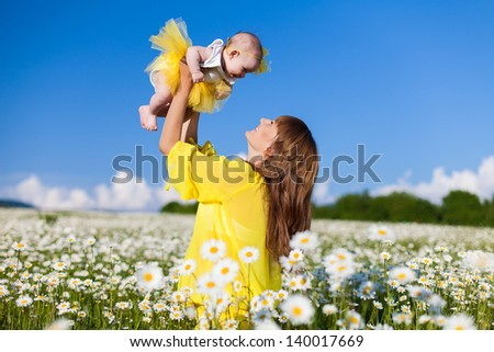 Beautiful young mother playing with her daughter in field of daisies