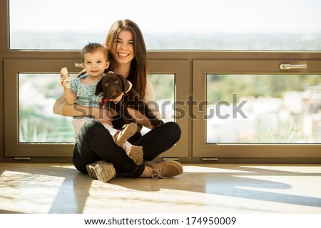 Beautiful young mother sitting at home with her daughter and their cute Labrador puppy - stock photo