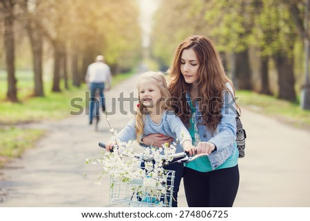 Beautiful young mother teaching her daughter to ride a bicycle. Both smiling, summer park in background, active family concept - stock photo