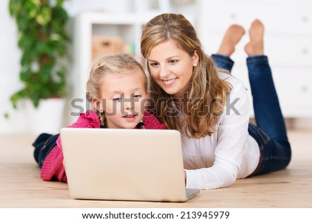 Beautiful young mother teaching her little daughter as they lie on the living room floor together sharing a laptop computer reading the screen - stock photo