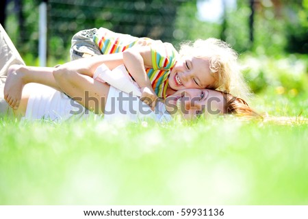 Beautiful young mother with her  daughter playing on grass . summer. - stock photo