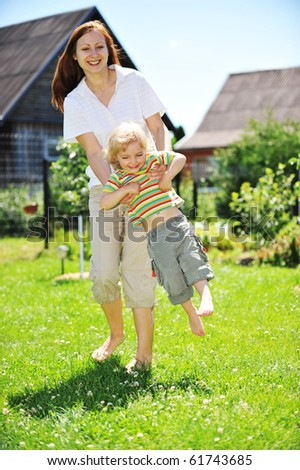 Beautiful young mother with her  daughter playing on grass . summer.