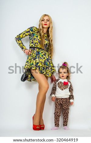 Beautiful young mother with her daughter standing - stock photo