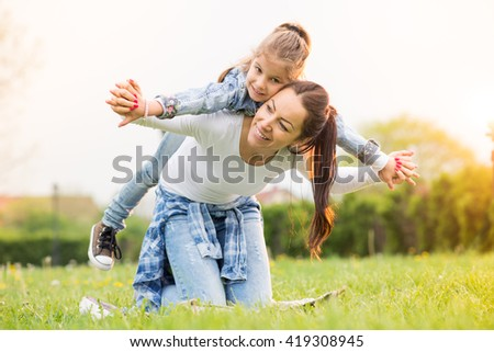 Beautiful young mother with her five years old daughter laying on the grass,and playing ,colored photo