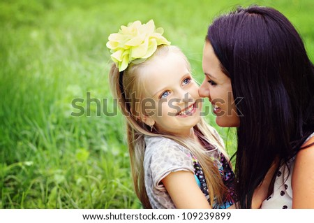 Beautiful young mother with her five years old daughter playing on the grass - stock photo