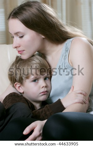 beautiful young mother with her little son on the sofa - stock photo