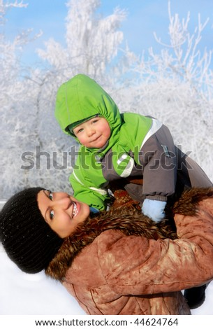 beautiful young mother with her little son outdoors