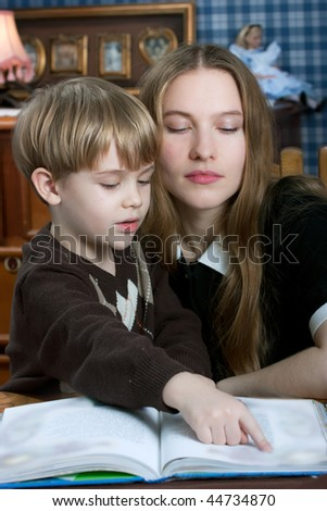 beautiful young mother with her little son reading the book at the table