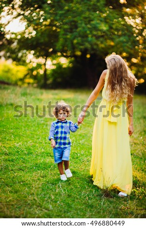 beautiful young mother with her son walking together in a park