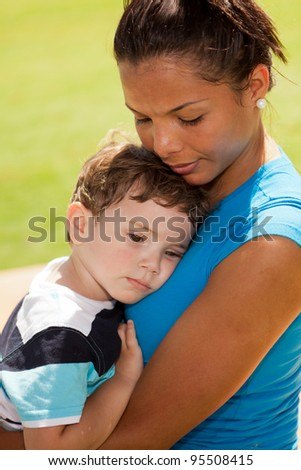 Beautiful young multicultural woman and boy in a outdoor park setting. - stock photo