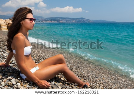 Beautiful young multicultural woman enjoying the beach in Nice in the French Riviera. - stock photo