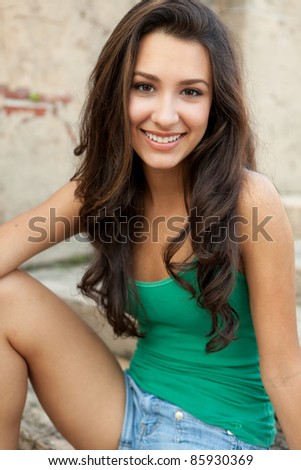 Beautiful young multicultural woman in an outdoor setting. - stock photo
