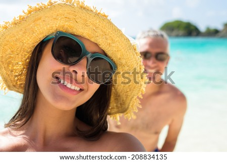 Beautiful young multicultural woman taking a selfie at the beach with a photobomber in the background. - stock photo